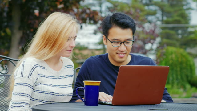 Multiethnic team working together. Asian man and Caucasian woman working with a laptop. On the summer terrace or cafe video