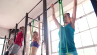 Multi-ethnic teen friends exercising pull-ups  at the gym video