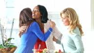 Multi-ethnic women in kitchen greeting, hugging video