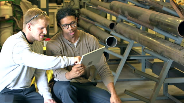 Multi-ethnic young men in factory with digital tablet video