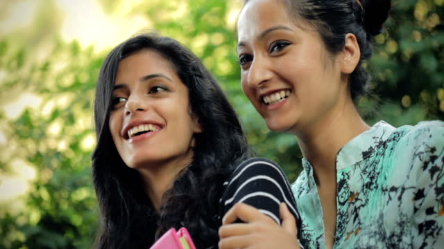 Multi-ethnic young women together in fresh air with books. video