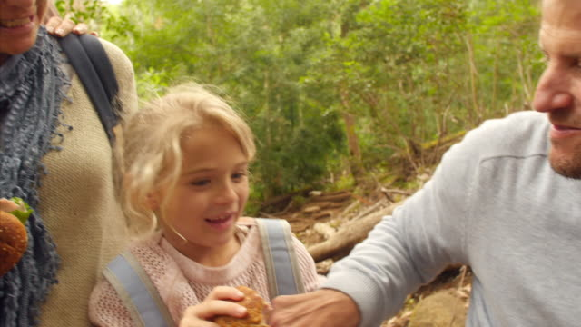 Multi-generation family eating outdoors during a hiking trip video