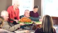Multi-generation family having Thanksgiving turkey meal video