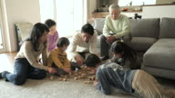 Multi-generation Family playing in the block of wood in the living room video