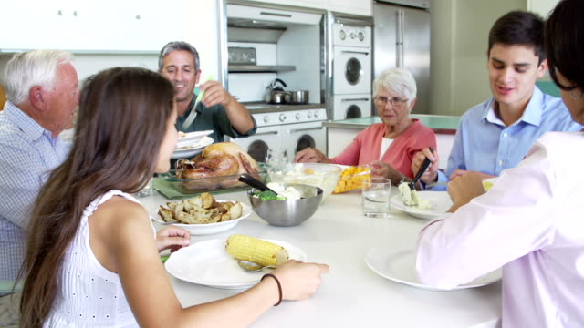 Multi-Generation Family Sitting Around Table Eating Meal video