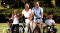Multigeneration family standing in a park with their bicycles video