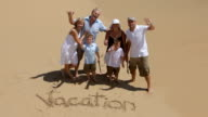 Multi-generation family writes VACATION in the sand video