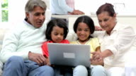 Multi-Generation Indian Family With Laptop Sitting On Sofa video