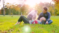 Multinational friends relaxing in a park. Autumn day at sunset. With them, a dog, a woman uses tablet video