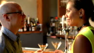 Multiracial couple at bar toasting martinis video