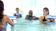 Multiracial older women in water aerobics exercise class video
