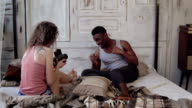 Multiracial photoshoot. Photographer woman taking photo of funny man in pajamas on moving-film camera on the bed video