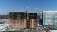 Multi-storey building under construction and building cranes video