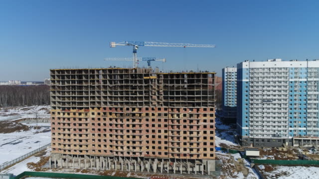 Multi-storey building under construction and building cranes video