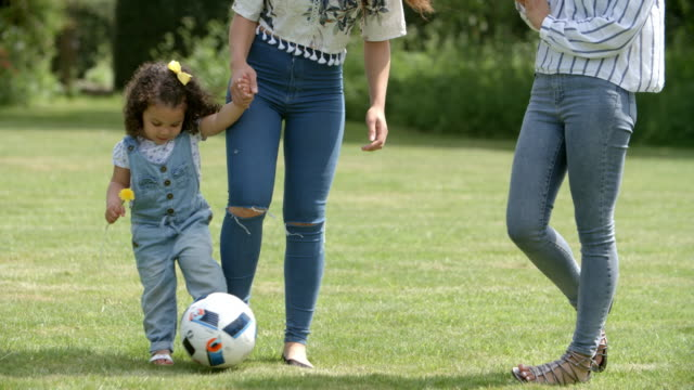 Mum and friends kicking a ball outdoors with young daughter video