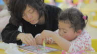 mum, asian girl cooperate on coloring picture in the kindergarten. video