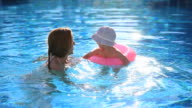 Mum with a small daughter swim in the pool with pink lifeline. video