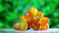 Muscat grapes cluster rotating on green outdoor background video