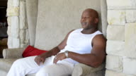 Muscular African man sitting relaxed video