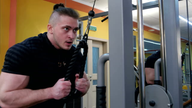 Muscular body builder working out at the gym on a cable machine video