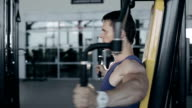 Muscular bodybuilder doing exercises workout in gym for breast muscles. Full face shot video