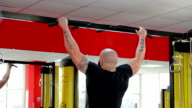 Muscular bodybuilder with strong body doing chin-up exercises, training at gym video