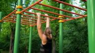Muscular man doing pull-ups on horizontal bar video