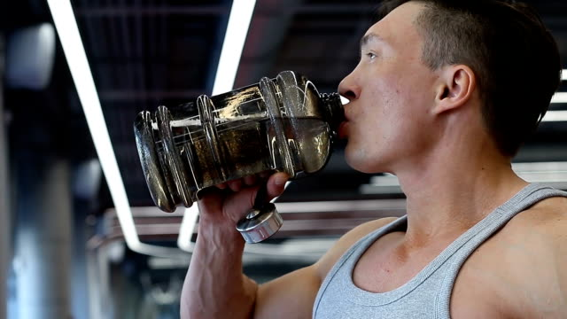 Muscular man drinking water after grueling workout video
