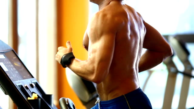 Muscular man exercising on a treadmill. video