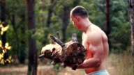 Muscular man lifting a heavy log video