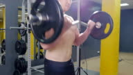 Muscular man working out in gym doing exercises with barbell at biceps video