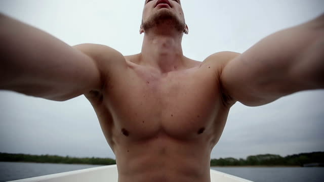 Muscular strong man floating on a boat. Slow motion. video