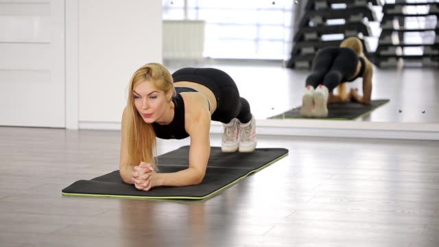 A muscular woman athlete performs a plank in the gym. Load abdominal muscles, back video