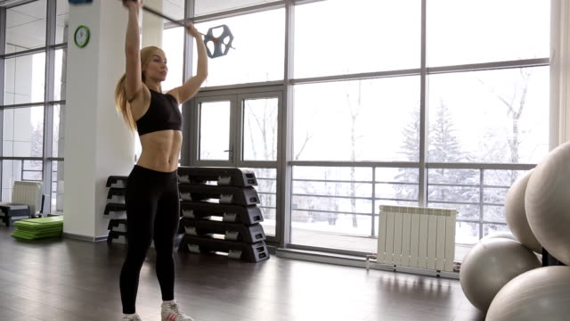 A muscular woman athlete using gym in the gym. back, legs, arms, shoulders video