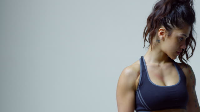 Muscular woman in sports clothing flexing bicep to camera, shot on R3D video