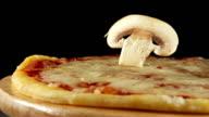 Mushroom slice falls on a pizza on a black background video