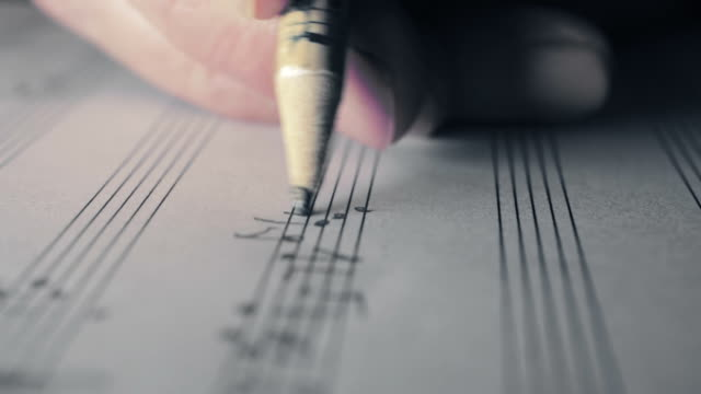 music writing: close up footage of musician composing with a pencil: staff, key video