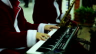 Musical band in Santa Claus suits playing merry melody to video