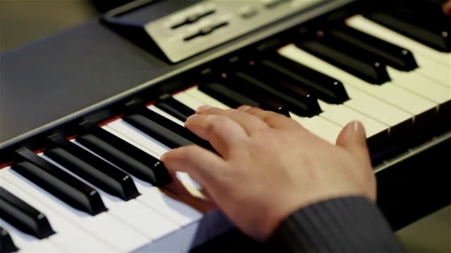 Musician playing keys of synthesizer keyboard – fingers hands close up video