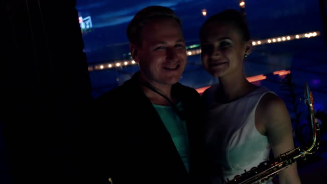 Musician with saxophone posing with girl for photo on party in nightclub. Dance video