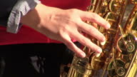 Musician's  female hand playing on saxophone  during a musical performance video