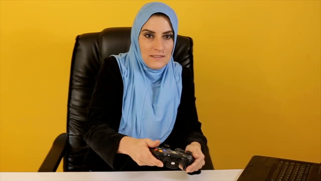 Muslim businesswoman playing games on the work video