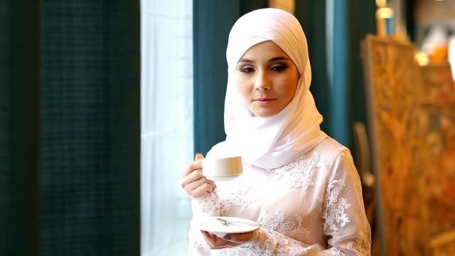 Muslim Girl Drinking Tea In Cafe video