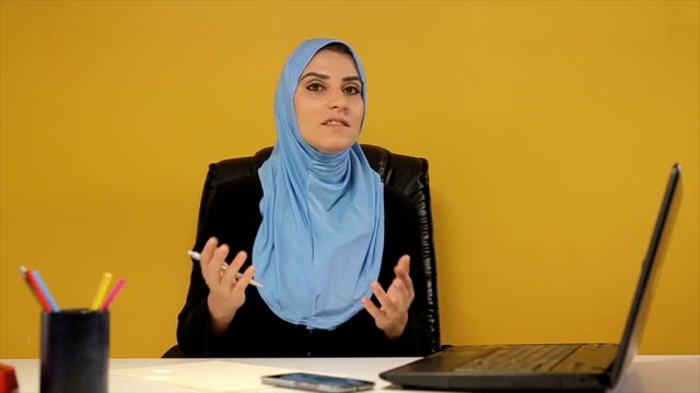 A Muslim woman leader gives a lecture to her employees video