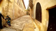 Muslim Woman with Child and Man with Briefcase Go on Old Narrow Paved Street Urfa video