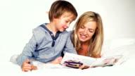 mutter und sohn liegen im bett und schauen gemeinsam ein familien fotobuch an video