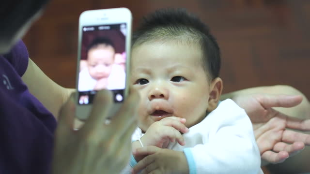 My baby taking a picture on mobile phone video