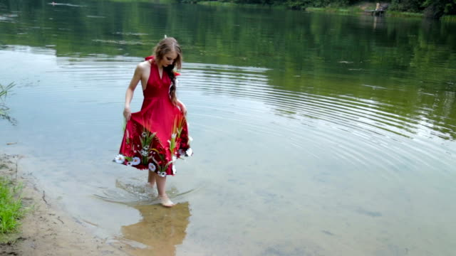 Mysterious girl with creative make-up in ethnic red dress walking in water video