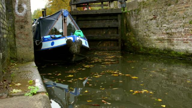 Narrowboat passing river lock video