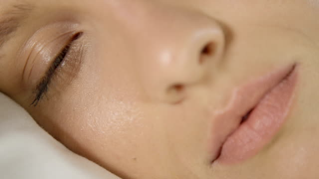 CLOSE UP DOF: Naturally beautiful Caucasian girl sleeping, waking up and smiling video